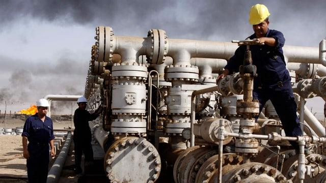 Arbeiter an einem Rorleitungssystem für Erdöl.