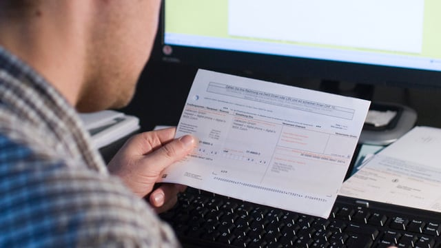 Ein Mann hält einen Einzahlungsschein in den Händen.