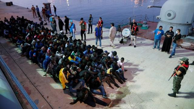 Dutzende Afrikaner sitzen auf einer Mole am Boden, Helfer und Bewaffnete stehen darum herum.