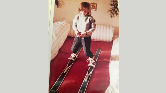 Foto aus den 60er-Jahren mit einem Kind auf Ski in einem Wohnzimmer.