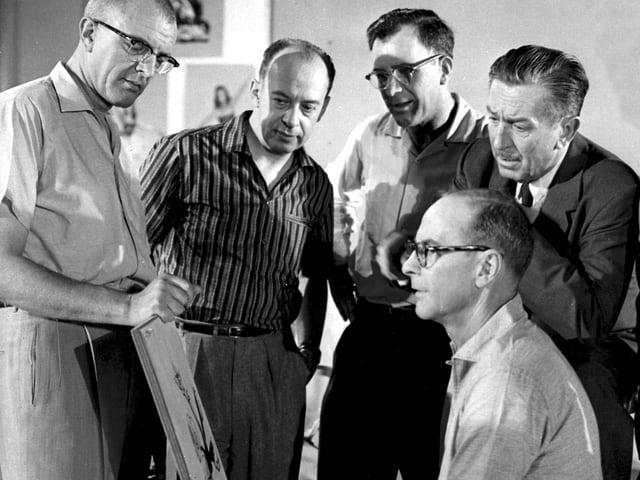 Vier Männer stehen um eine Staffelei herum, einer sitzt davor.