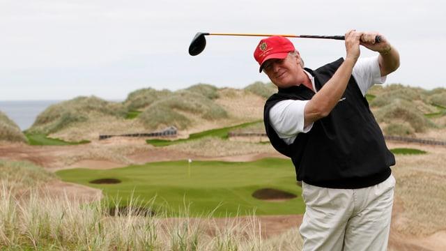 Trump mit Golfschläger auf Golfplatz.