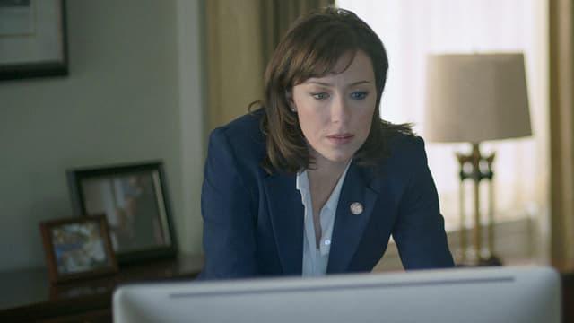 Eine Frau beugt sich über den Tisch vor einem Bildschirm.