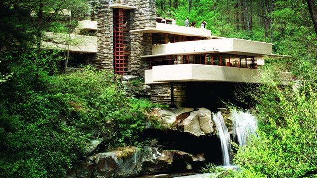 Ein Haus steht im Wald auf einem Wasserfall.