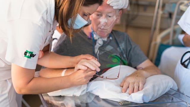 Eine Krankenschwester kümmert sich um einen Patienten.