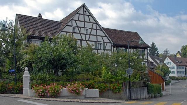 Ein Riegelhaus in Oberwil an einer Strassenkreuzung mit zwei Strassenlaternen