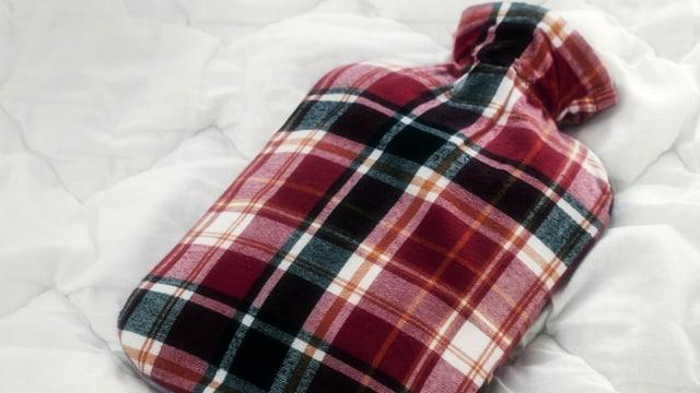 Wärmflasche mit Schottenkaros auf einer Daunendecke.