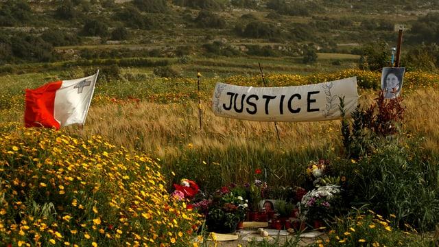 """Banner mit der Aufschrift """"Gerechtigkeit"""" am Ort des Anschlags"""