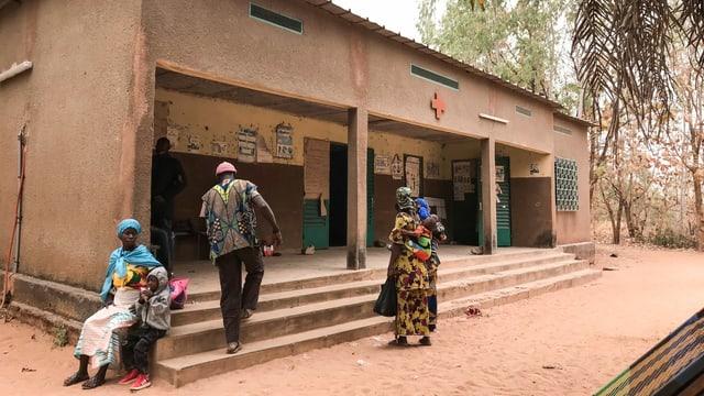 Lehmhaus mit einem Roten Kreuz über dem Eingang. Davor sind mehrere dunkle Personen mit traditionellen Kleidern.