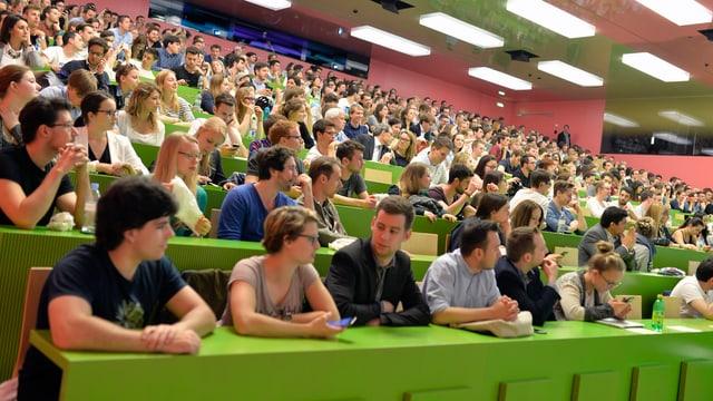 Symbolbild: Studenten in einem Vorlesungssaal mit grünen Pultreihen.