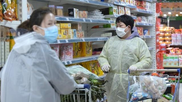 Zwei Menschen in Supermarkt mit Maske und Schutzkleidung