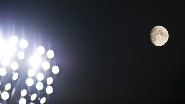 Flutlichter eines Fussballstadions leuchten in der Nacht, am Himmel der Mond.