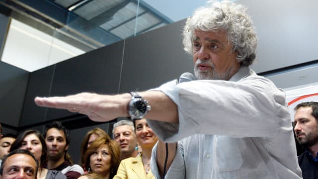 Grillo gestikuliert bei einer Medienkonferenz im April 2013, im Hintergrund Zuschauer.