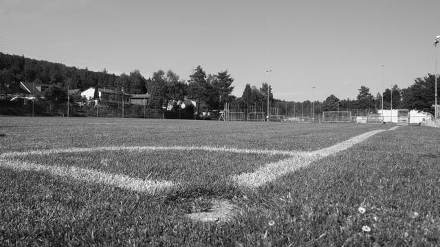 Eine Schwarz-Weiss-Aufnahme eines Fussballplatzes, fotografiert vom Boden aus mit Blick aus dem Cornerfeld heraus.