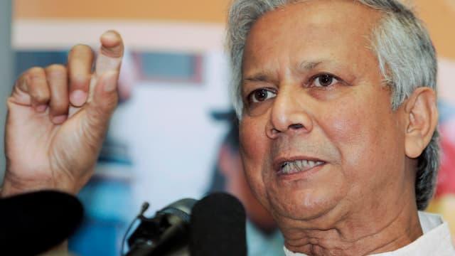 Friedensnobelpreisträger Muhammad Yunus spricht in Mikrofone.