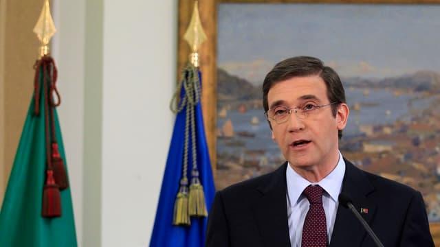 Pedro Passos Coelho spricht vor zwei Flaggen und einem Gemälde in ein Mikrofon.