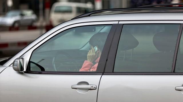 Eine Frau telefoniert mit ihrem Handy am Steuer ihres Autos.