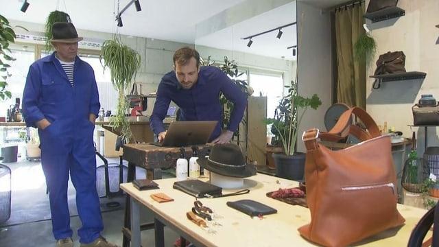 Zwei Männer in einem Geschäft. Auf einem Tisch stehen Ledertaschen.