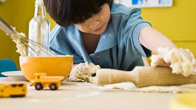Kleiner Junge walzt einen Teig mit dem Nudelholz