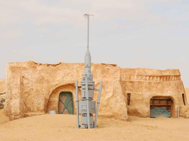 Wüstenhäuser aus Sand, davor eine Art Antenne.