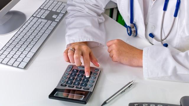 Arzt tippt auf Taschenrechner