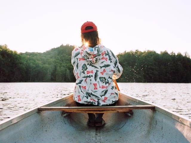 Rückenansicht eines Mannes, der in einem Boot auf einem See sitzt.