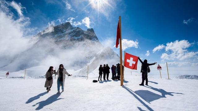 Touristen im Schnee mit Schweizer Fahne und Bergen.