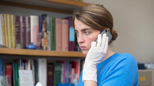 Eine junge Frau hält sich mit weissen Gummihandschuhen ein Mobiltelefon gegen das Ohr.