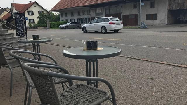 Stühle und Bartische an einer Strasse.