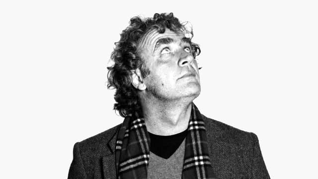Alex Capus porträtiert in Schwarzweiss, er blickt nach oben.