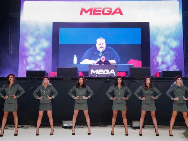 Sechs Tänzerinnen in Militäruniform und kurzem Rock stehen vor einer Videoleinwand, auf der Kim Dotcom zu sehen ist, wie er in ein Mikrophon spricht.