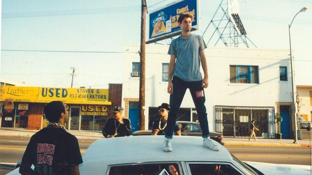 Ein MAnn steht auf dem Dach eines Autos. Neben dem Auto stehen drei weiter Männer.