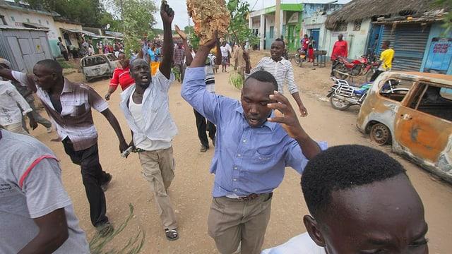Ein paar Männer schreiten durch eine Strasse in Hindi, Kenia, sie halten wütend die Arme in die Luft.