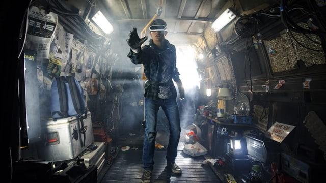 ein enger, chaotischer Raum, erleuchtet durch Neonröhren und ein kleines Fenster. Im Zentrum steht ein junge, eine Hand ausgestreckt, erstauntes Gesicht. Er trägt eine VR-Brille