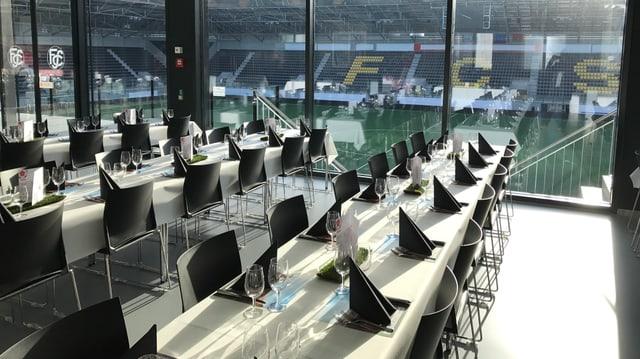 Stadion-Restaurant mit weissen Tischen und schwarzen Stühlen, dahinter Blick auf Tribüne und Rasen