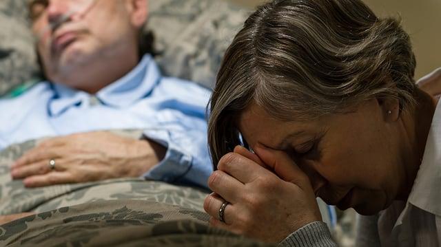 Frau trauert an Sterbebett