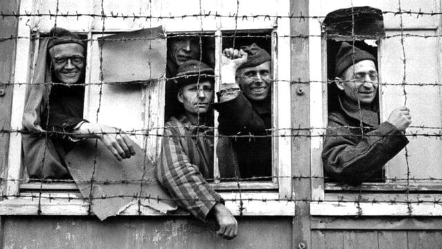 Gefangene von Dachau schauen aus Fenster. Ein Zaundraht schützt die Fenster.