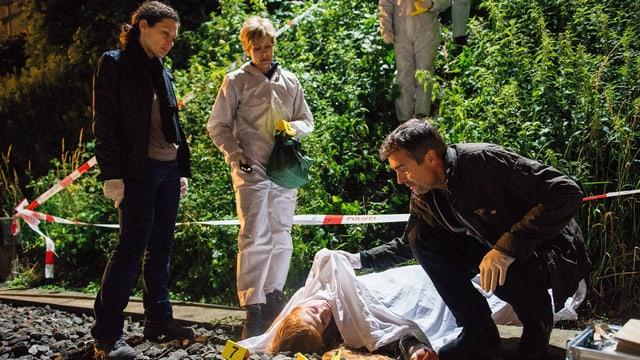 Ein Frau liegt tot am Boden. Ein Mann deckt sie mit einem Leinentuch zu. Zwei Frauen stehen dazu.