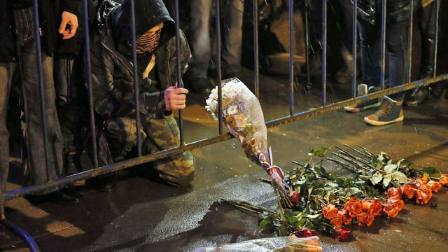 Menschen trauern am Tatort um den Oppositionspolitiker.