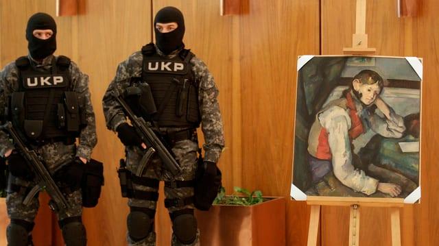 Bewaffnete Polizisten stehen neben dem Bild «Der Knabe mit der roten Weste».
