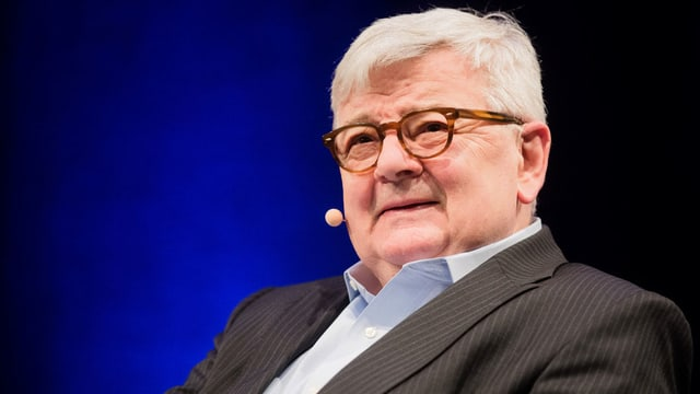 Ein Mann mit Brille, grauem Haar und umgeschnalltem Mini-Mikrophon.