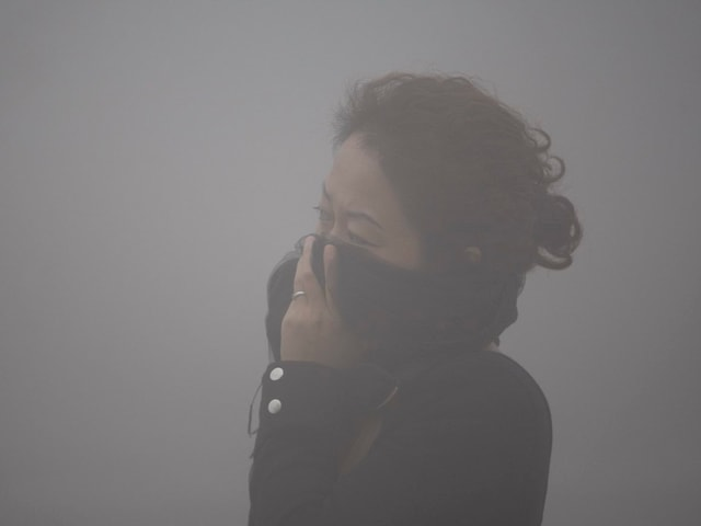 Frau im Smog schützt sich mit ihrer Kleidung