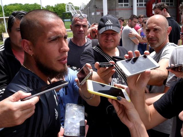 Jonatan Maidana spricht zur Presse, ihm werden iPhones entgegengestreckt.