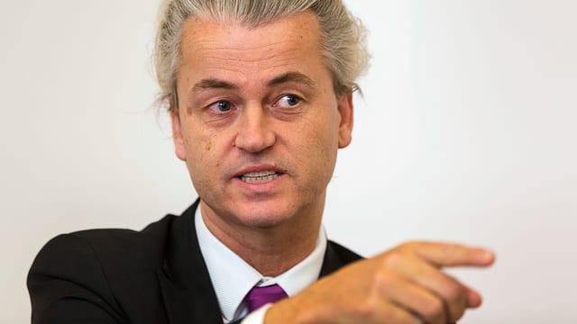 Brustbild von Wilders, der mit Zeigefinger auf die Seite deutet.