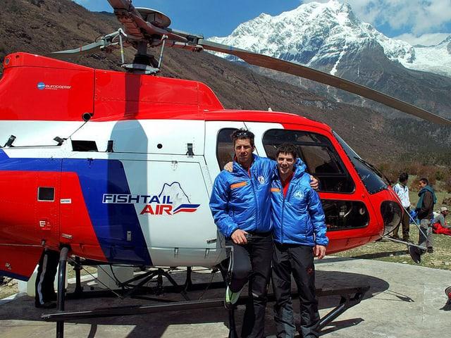 Richard Lehner und Daniel Aufdenblatten posieren in den Bergen vor einem Helikopter.