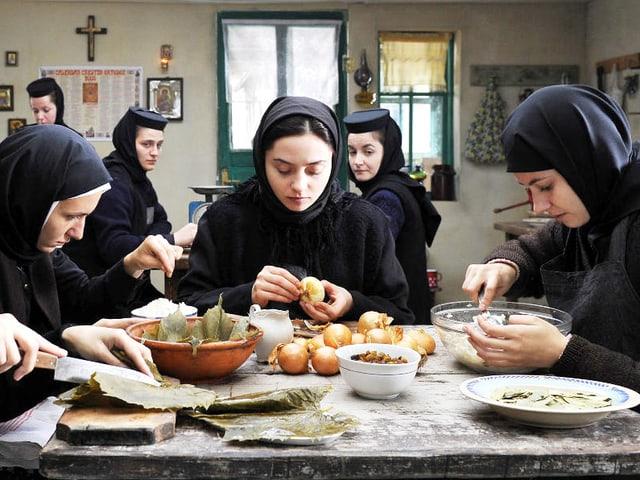 Nonnen am Tisch rüsten Gemüse.