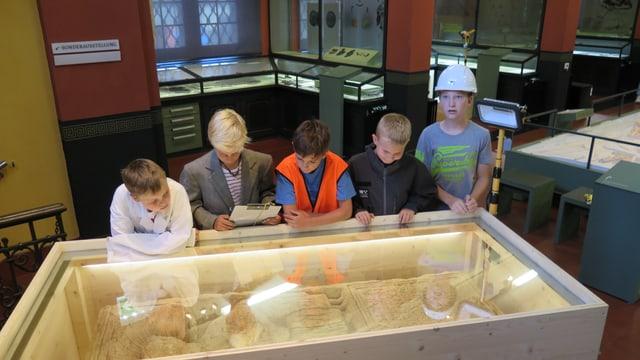 Fünf Jungs schauen in eine Glasvitrine, in welcher sich ein 2000 Jahre alter Grabstein befindet. Im Hintergrund ist das Museum zu sehen.