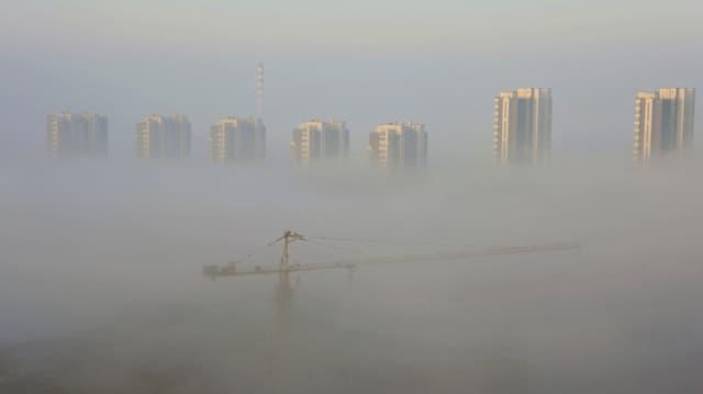 Eine Grossbaustelle in der chinesischen Metropole Shenyang, umhüllt von starkem Nebel