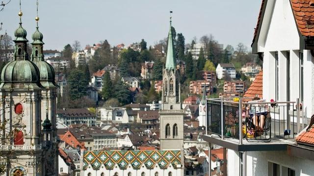 Ein Mann liest auf einem Balkon in der Stadt St. Gallen.