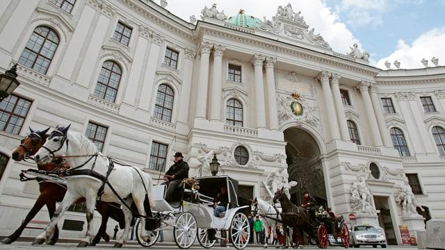 Mehrere Kutschen und ein Auto vor dem Eingang zur Hofburg in Wien.